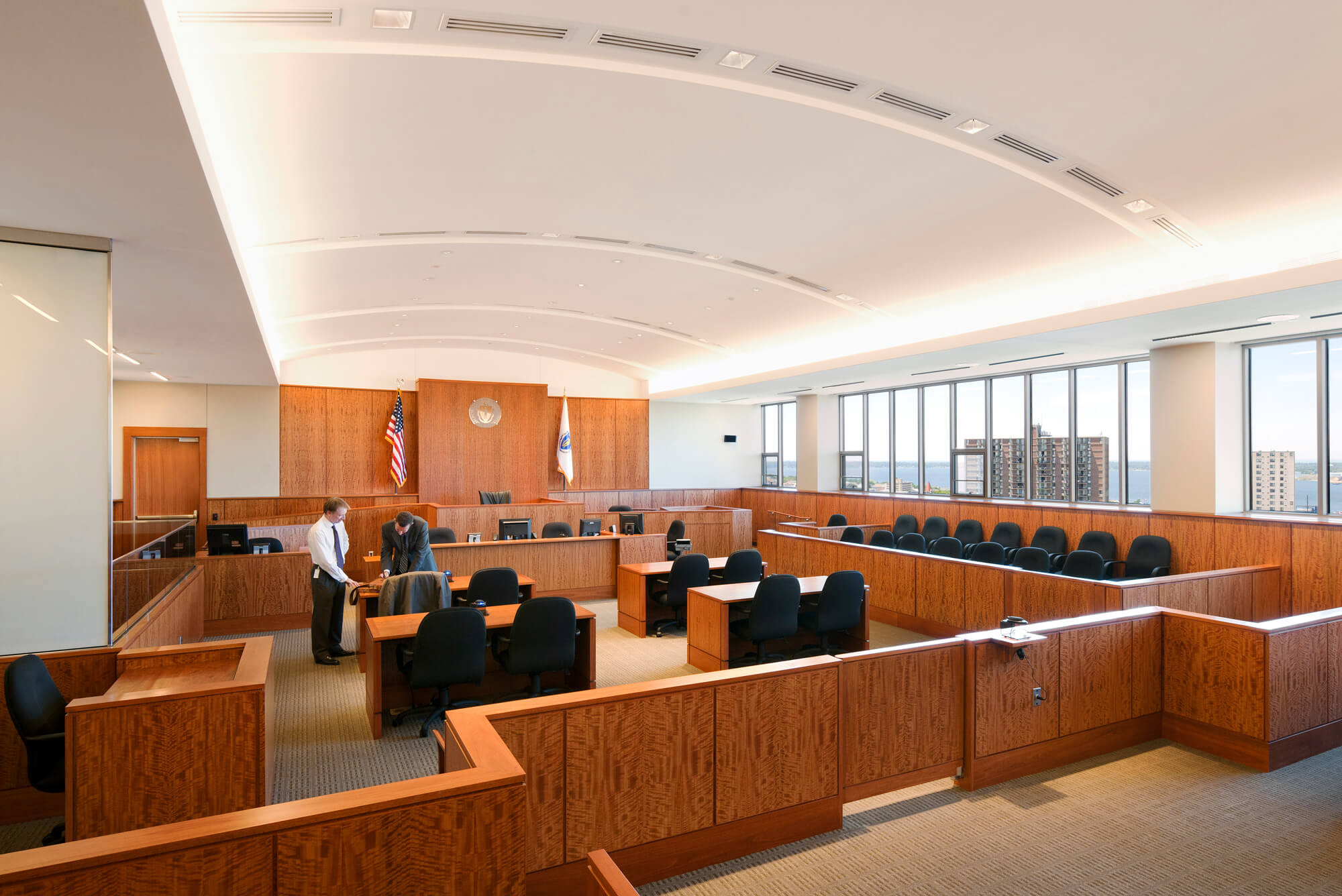 Interior of a courtroom with wooden furniture, natural light, and a slightly vaulted ceiling.