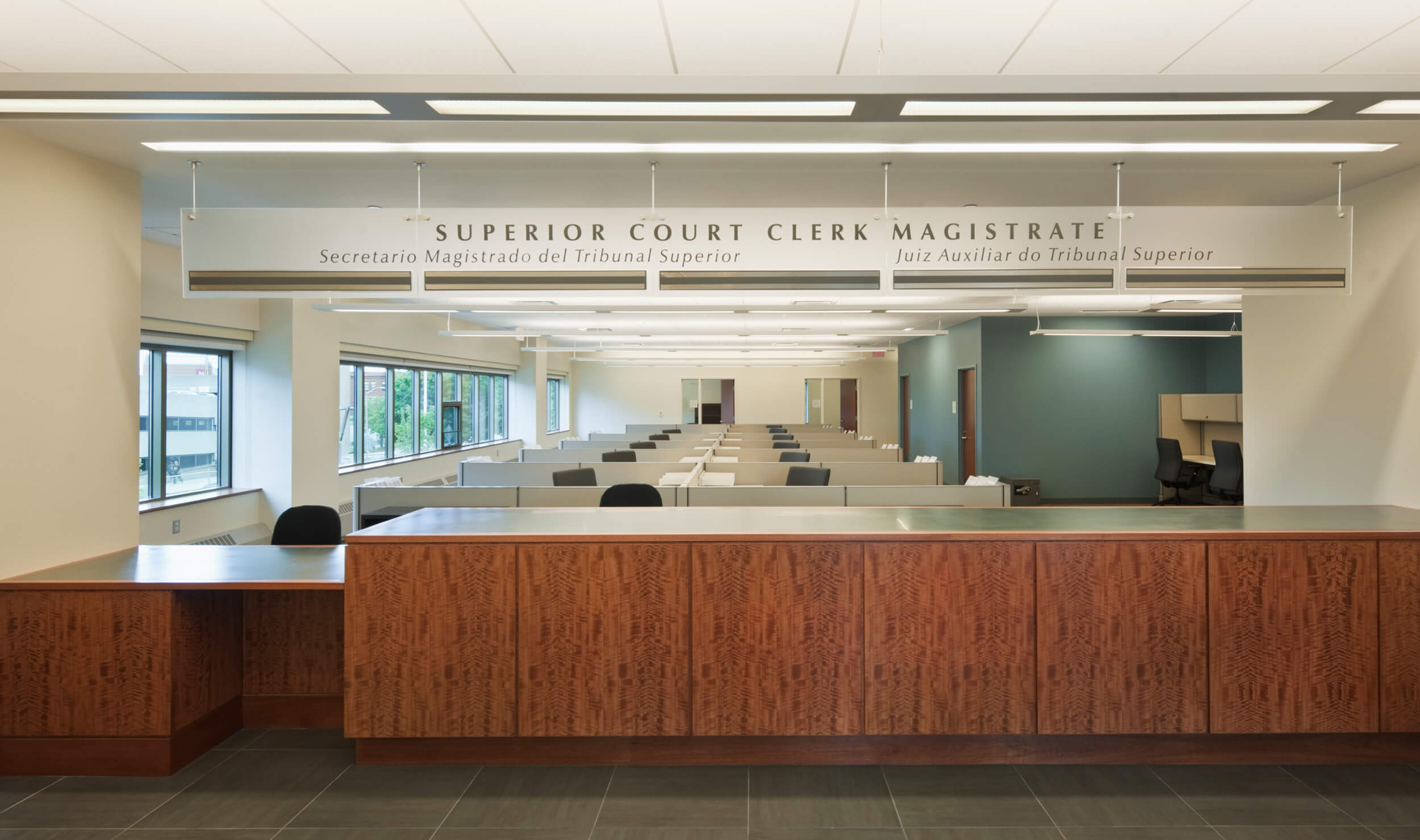 Superior Court Clerk Magistrate with wooden front desk and cubicles behind it.
