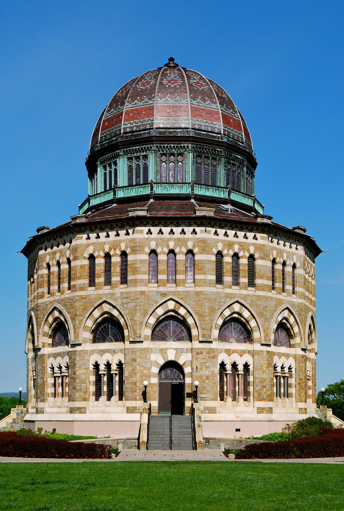 Frontal view of Nott Memorial at Union College, characterized by it's rounded stone shape, detailing around arced windows, and its red dome roof.