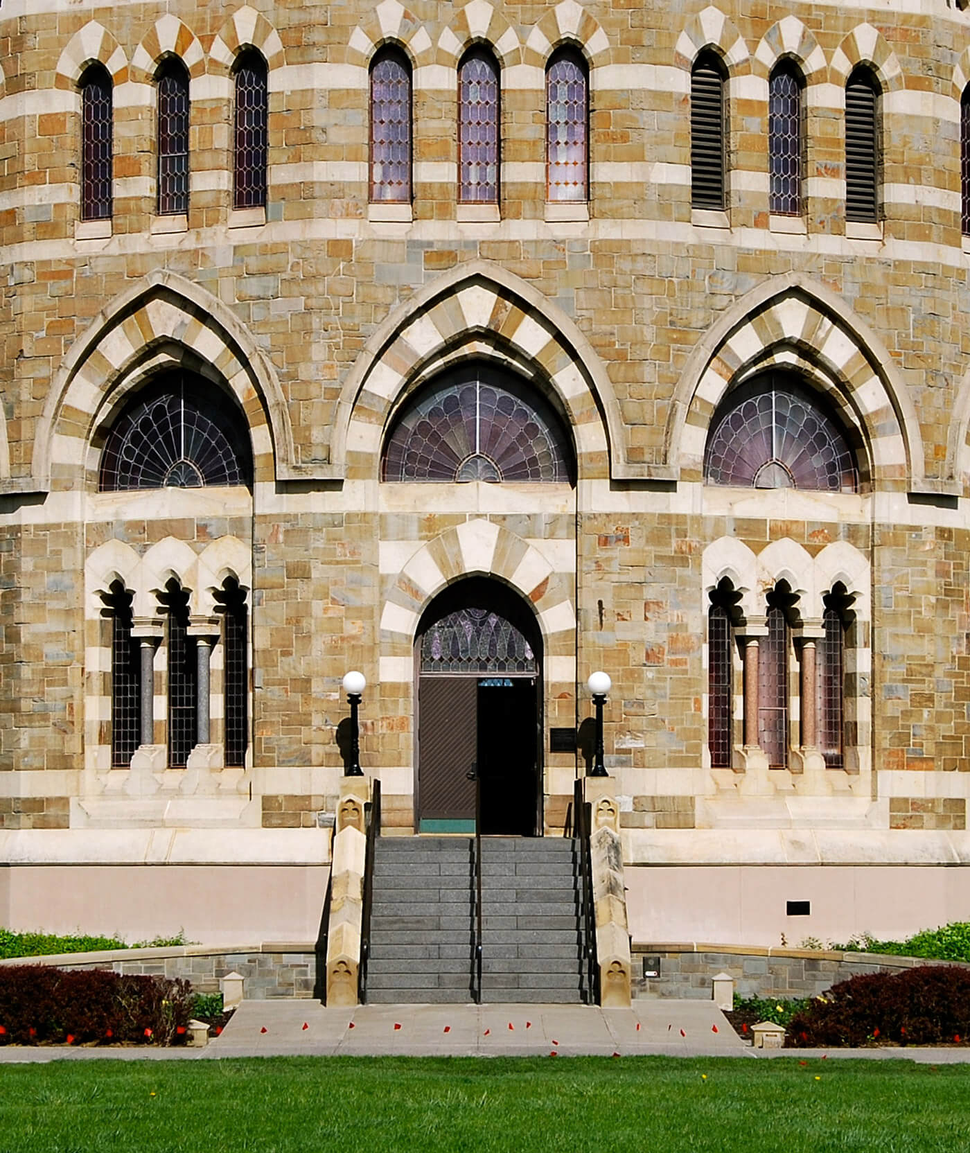 Close up shot of the entrance to Nott Memorial, with grey stairs leading up to an arced doorway, with colored stone patterns adorning the entry way and the windows.