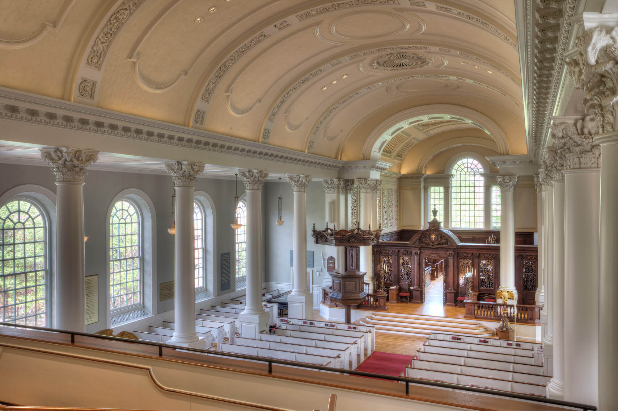 View from balcony onto the arched windows, columns, pews, and detailed vaulted ceiling.