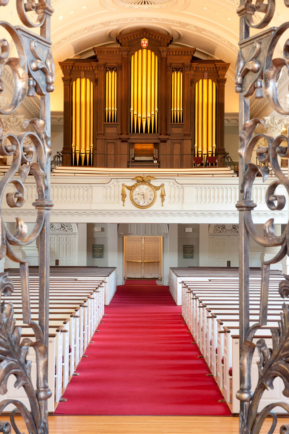 View onto the organ with white pews and red carpet in the foreground, framed by detailed metal gates.