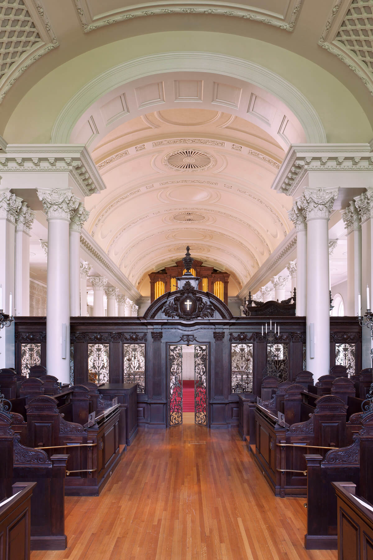 View from the chapel with dark wooden pews onto the wooden and metal gate, framed by columns.