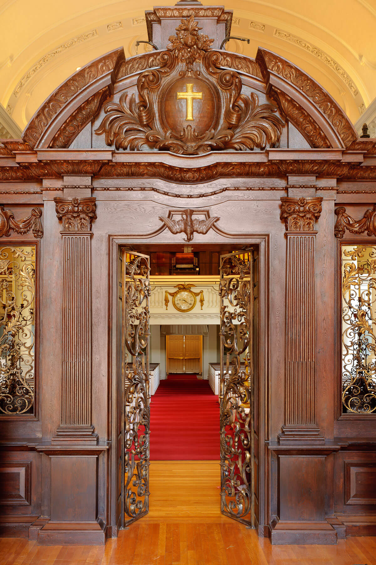 Elaborately carved wooden interior gate with detailed metal door opening onto wooden and red carpet floor.
