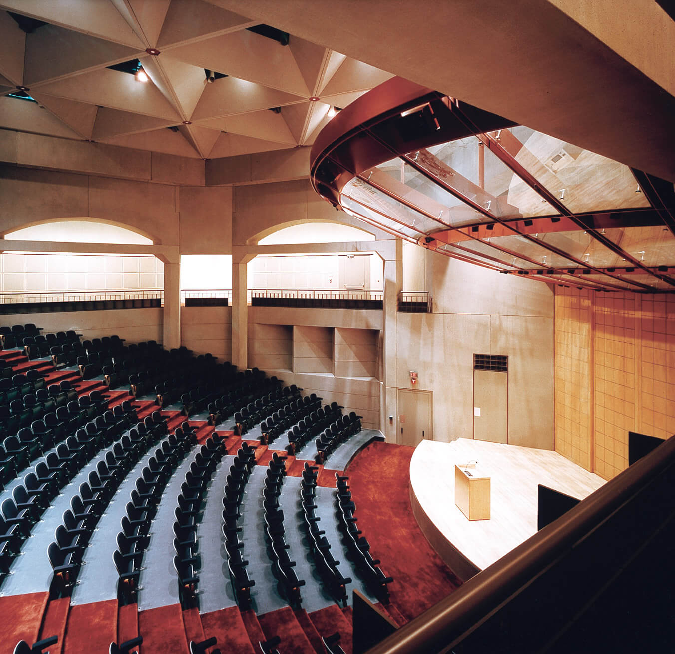 United State Holocaust Memorial Museum auditorium with red carpeting, blue seats, and stone walls with large geometric openings.