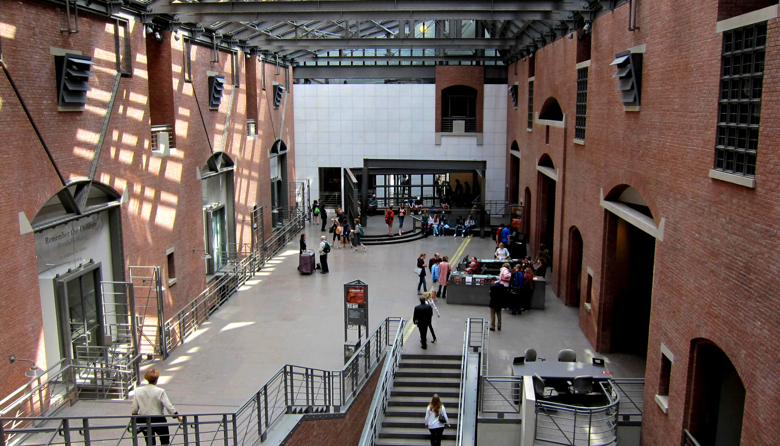 United States Holocaust Memorial Museum entrance atrium, composed of a steel and glass roof flanked by two brick facades with irregular openings.