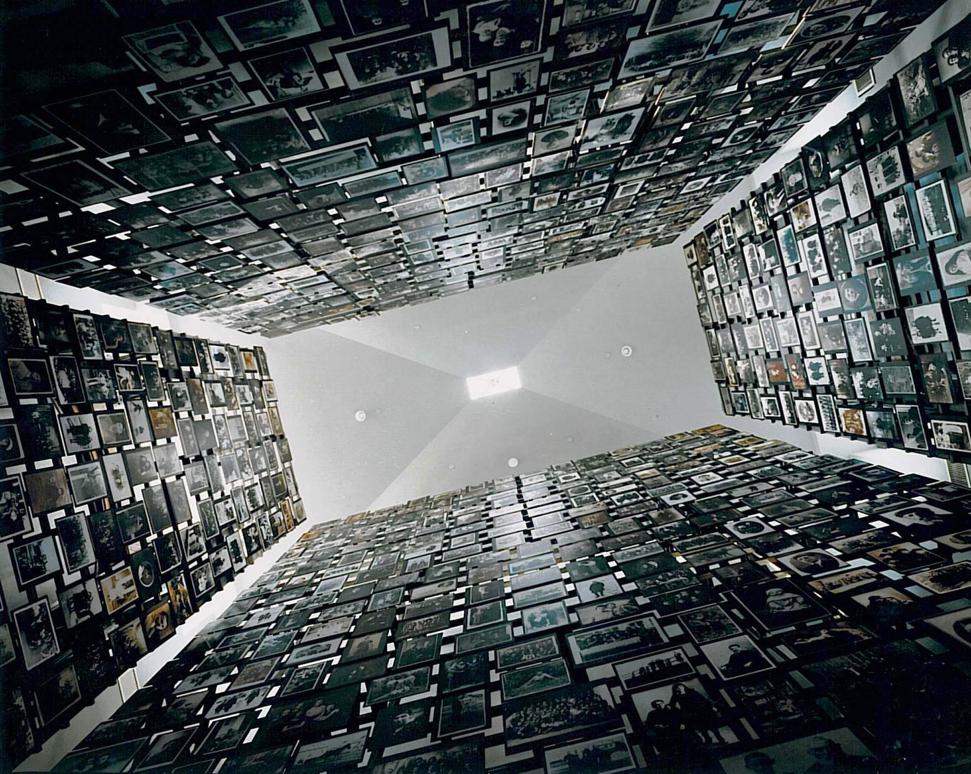 Tall rectangular space extended upwards and covered in framed photographs, a part of the permanent exhibition at the United States Holocaust Memorial Museum.