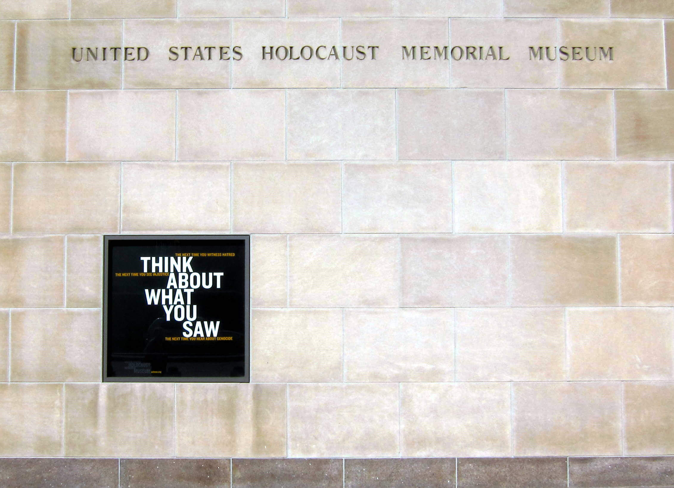 """""""Think about what you saw"""" panel inserted into a stone wall, with United States Holocaust Memorial Museum written above it."""