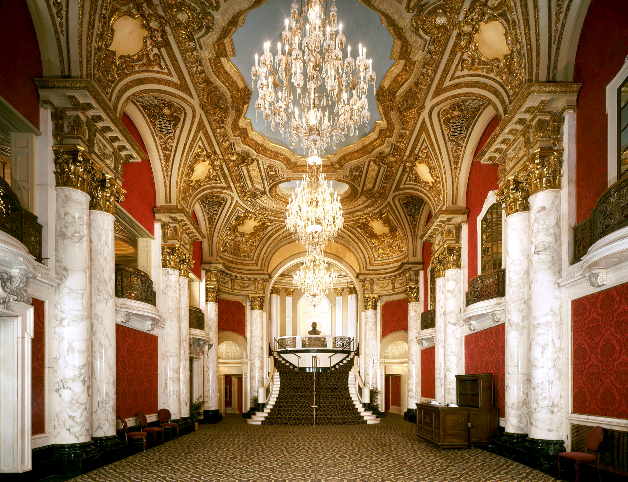 Ornate Entry hall with chandeliers, marble columns and red tapestries, with stairs in the background.