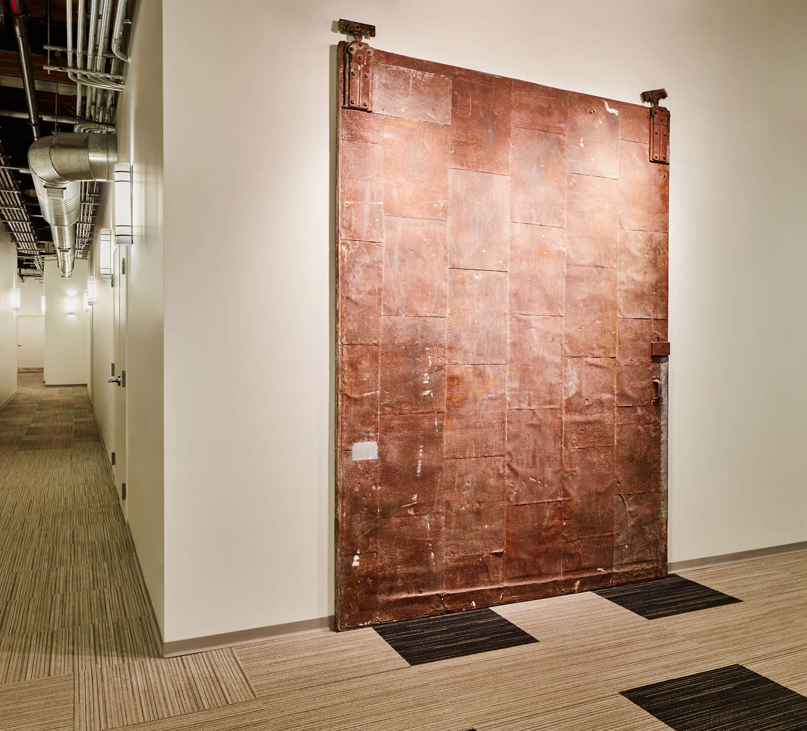 Copper door detail in a white hallway.