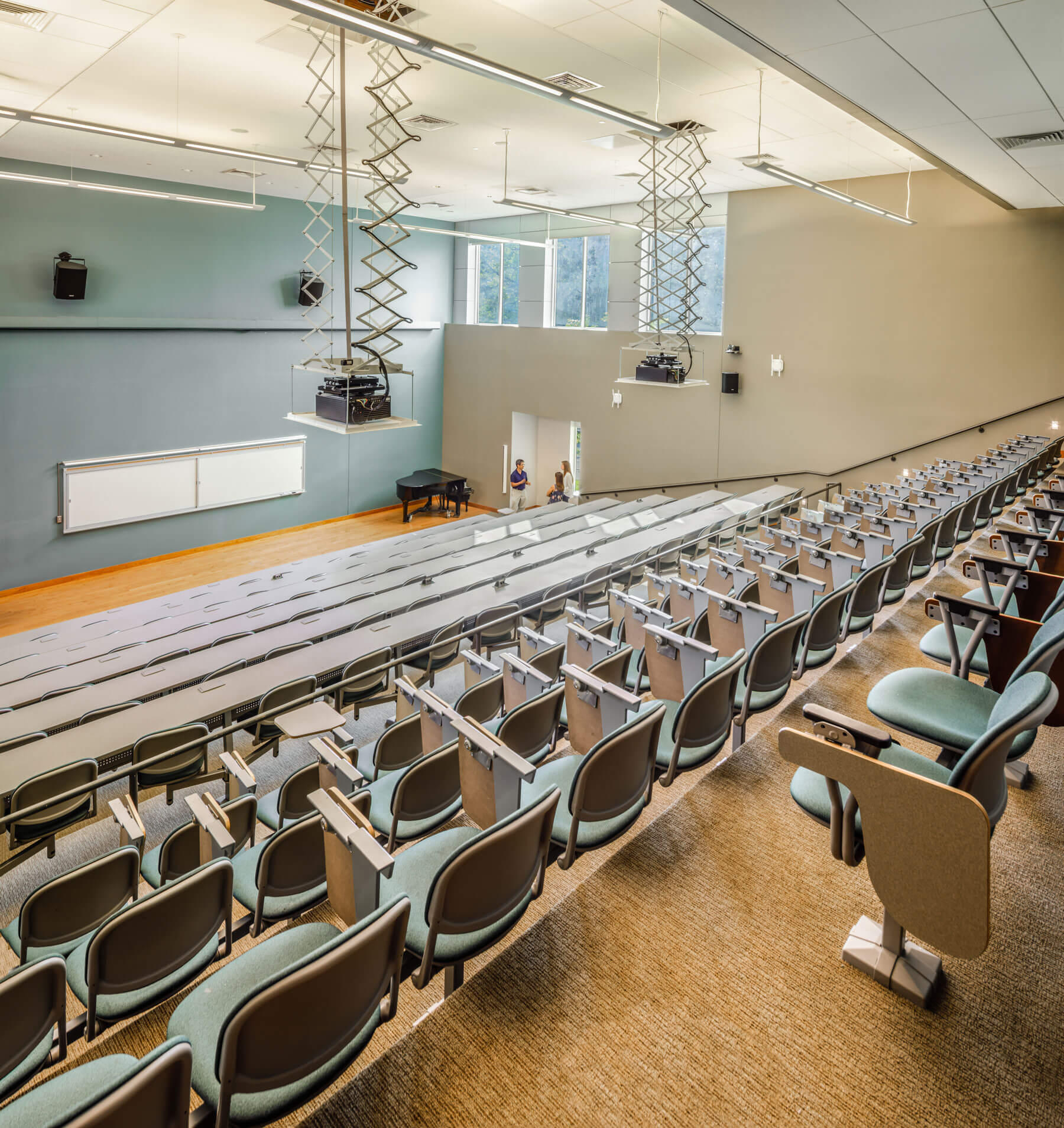 View at the top of row of a lecture hall with light blue-teal seats and walls, and a white board at the bottom in the front.