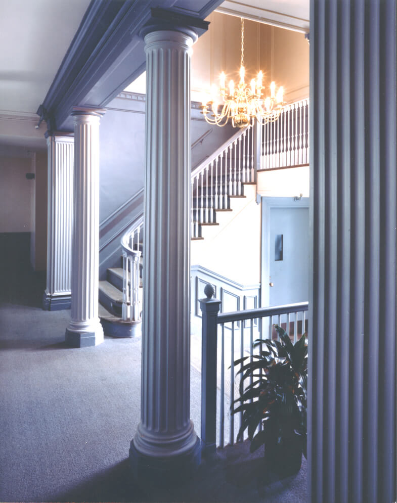 Angled view of a stairway with light blue colors, column, and a chandelier.