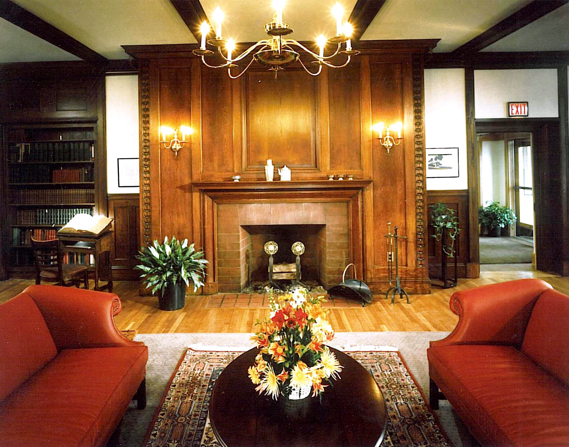 Interior view of a communal living area in one of the houses on Radcliff Quadrangle, with red couches around a coffee talve in teh foreground, and classical wooden fireplace in the background, with a bookshelf to the left.