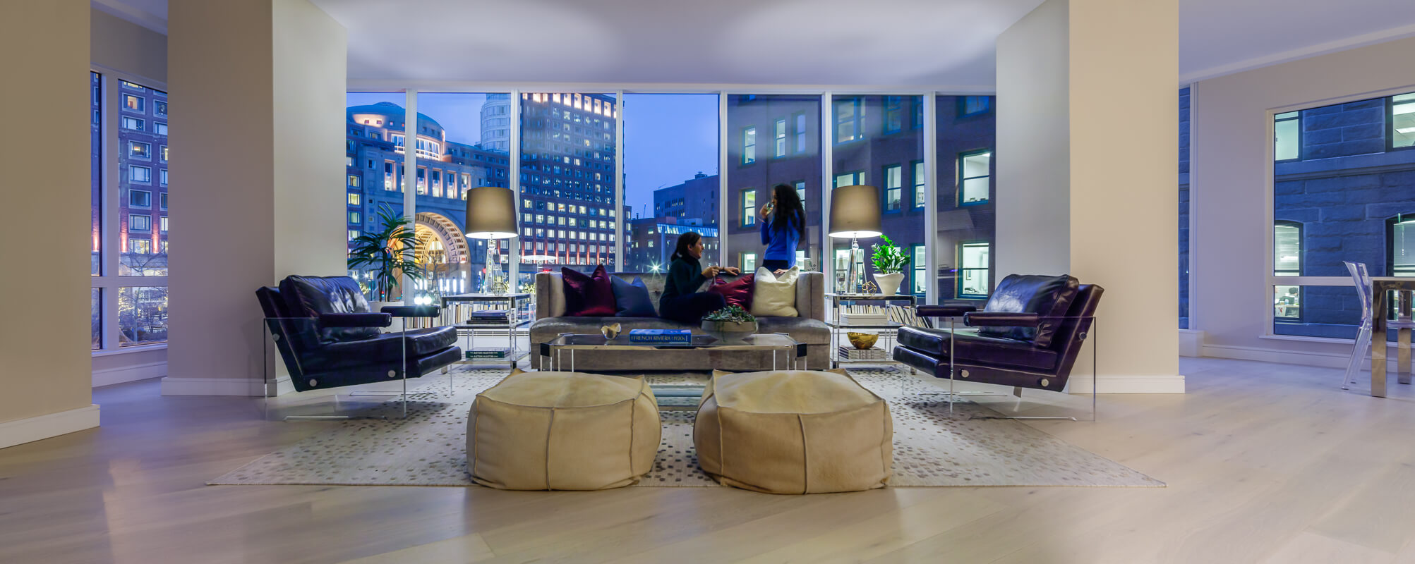 Woman on a couch drinking wine with another woman standing up in a modern, white apartment with large floor-to-ceiling windows revealing Boston buildings at dusk.