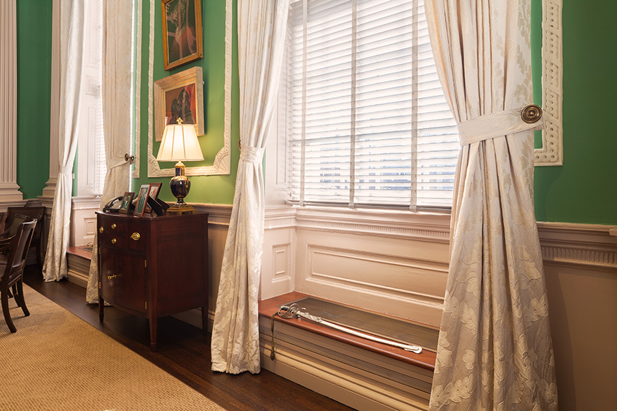 Sword on a window seat with silvery curtains and a small historic bureau with a lamp on it to the left.