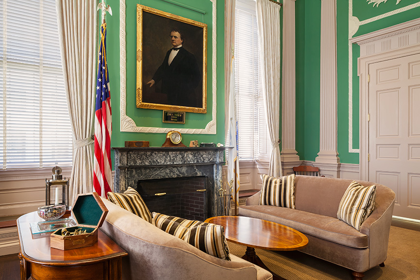 Two small sofas around a wooden coffee table in front of a historic, framed portrait and the American flag.
