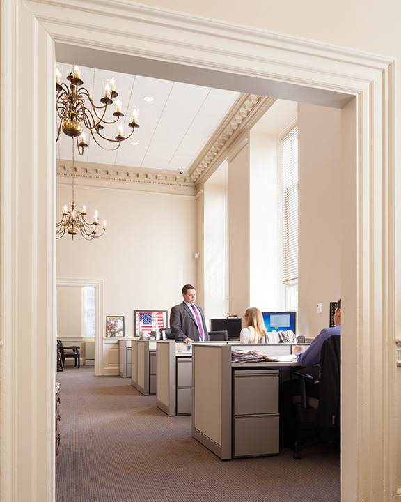 Standard office desks in a creme-colored space with historic chandeliers.
