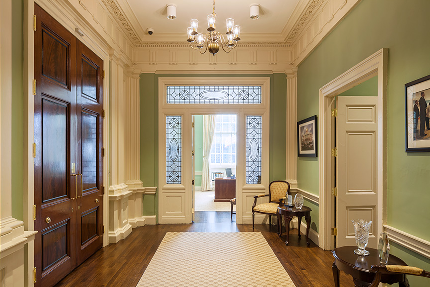 Hallway or transition space with an old chair and side table, in front of detailed wood and glass opening to another room.