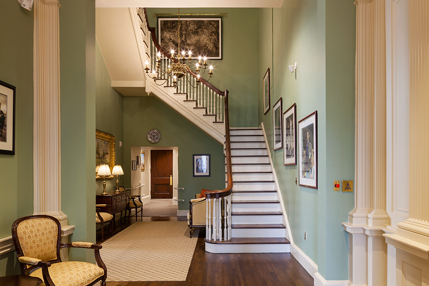 View of the stairs leading up to the second floor, with framed images, an old chair, and a historic chandelier.