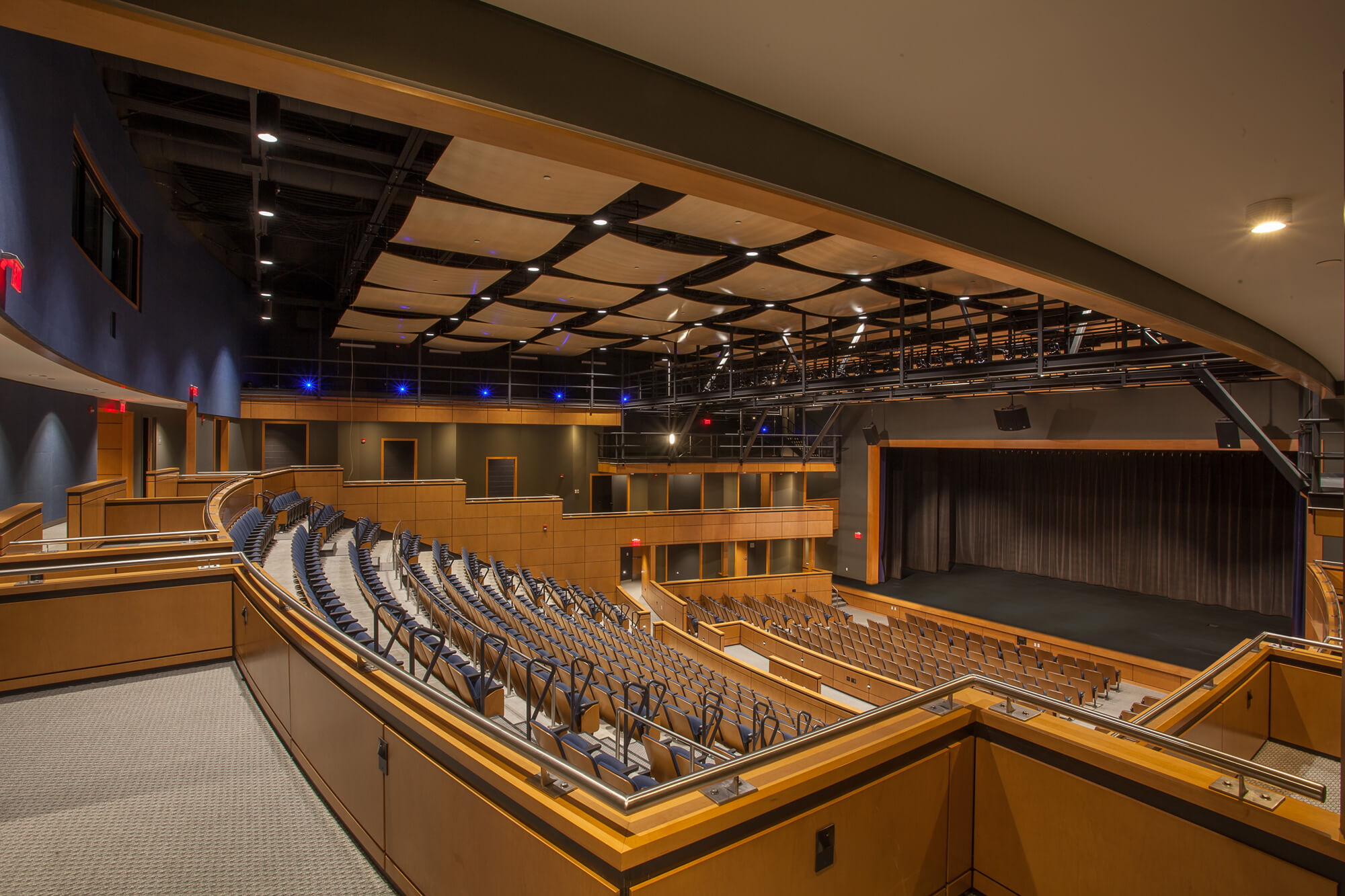 View of the auditorium with warm wooden tones and dark blue accents.