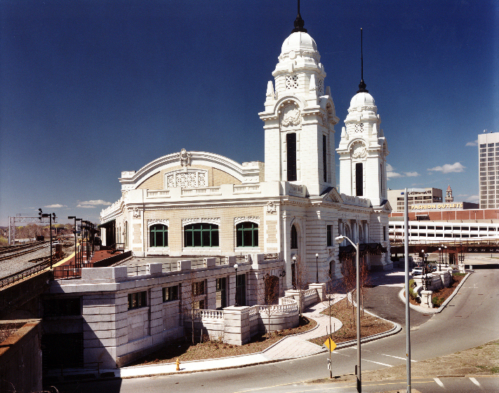 Exterior view of the Union Station Intermodal Transportation Center from the left, with a detailed side facade and recognizable white towers rising to the right on the front facade.