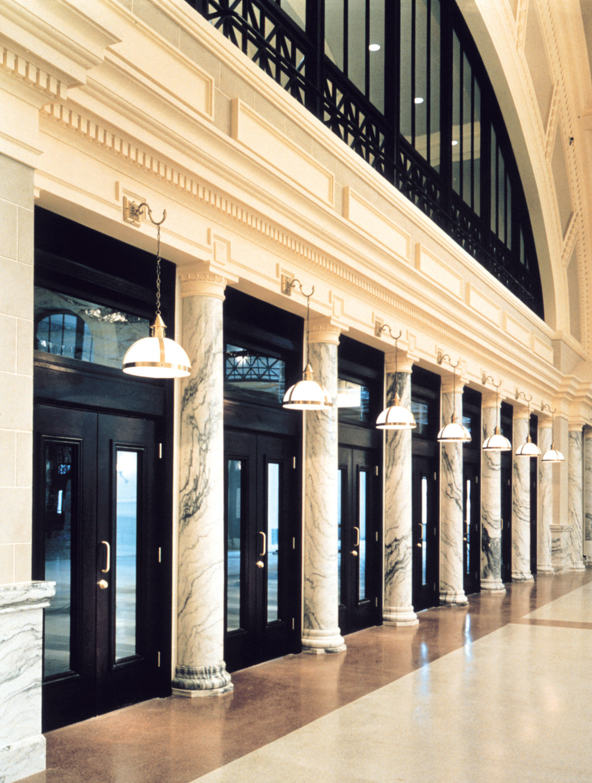 Entrance to the Union Station Intermodal Transportation Center from the inside, with black doors and ironwork, regularly interspersed with marbled columns.