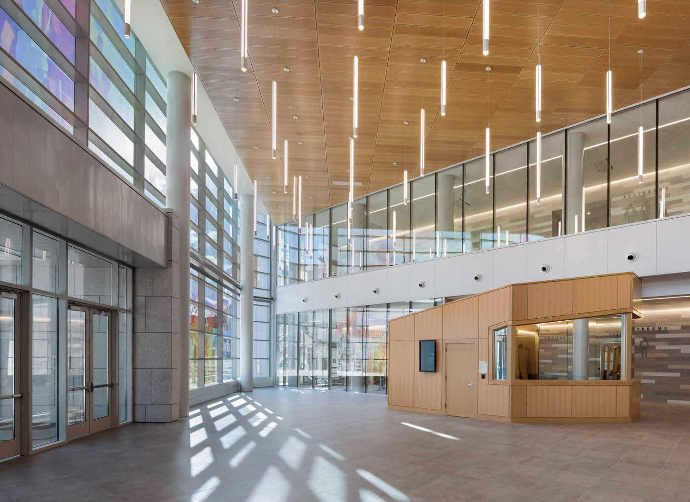 Inviting lobby of the Lowell Justice Center defined by tube-like lights, colorful art on the glass facade, and wooden accents.,