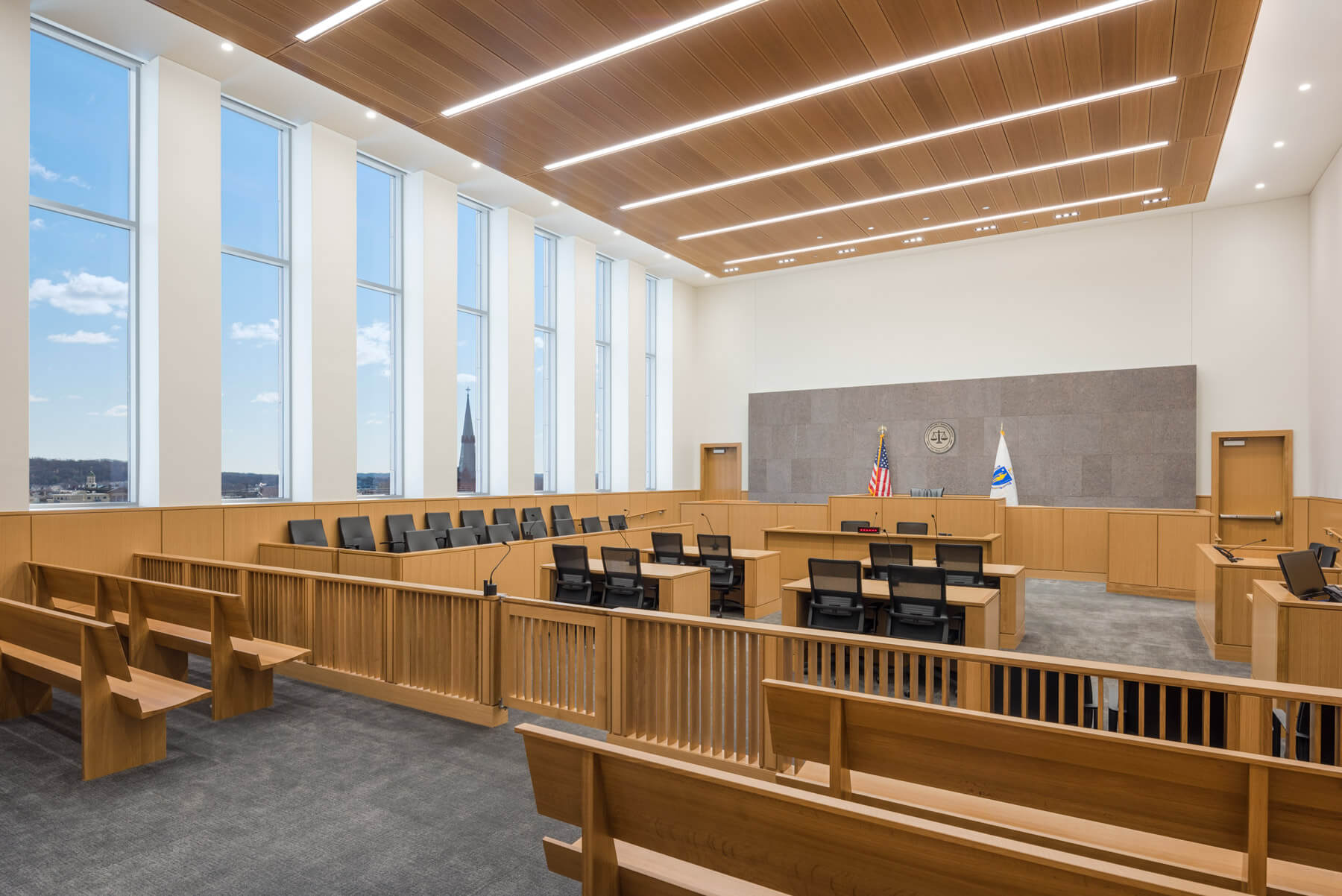 Angled view of warm, wooden courtroom with white walls and views of the sky.