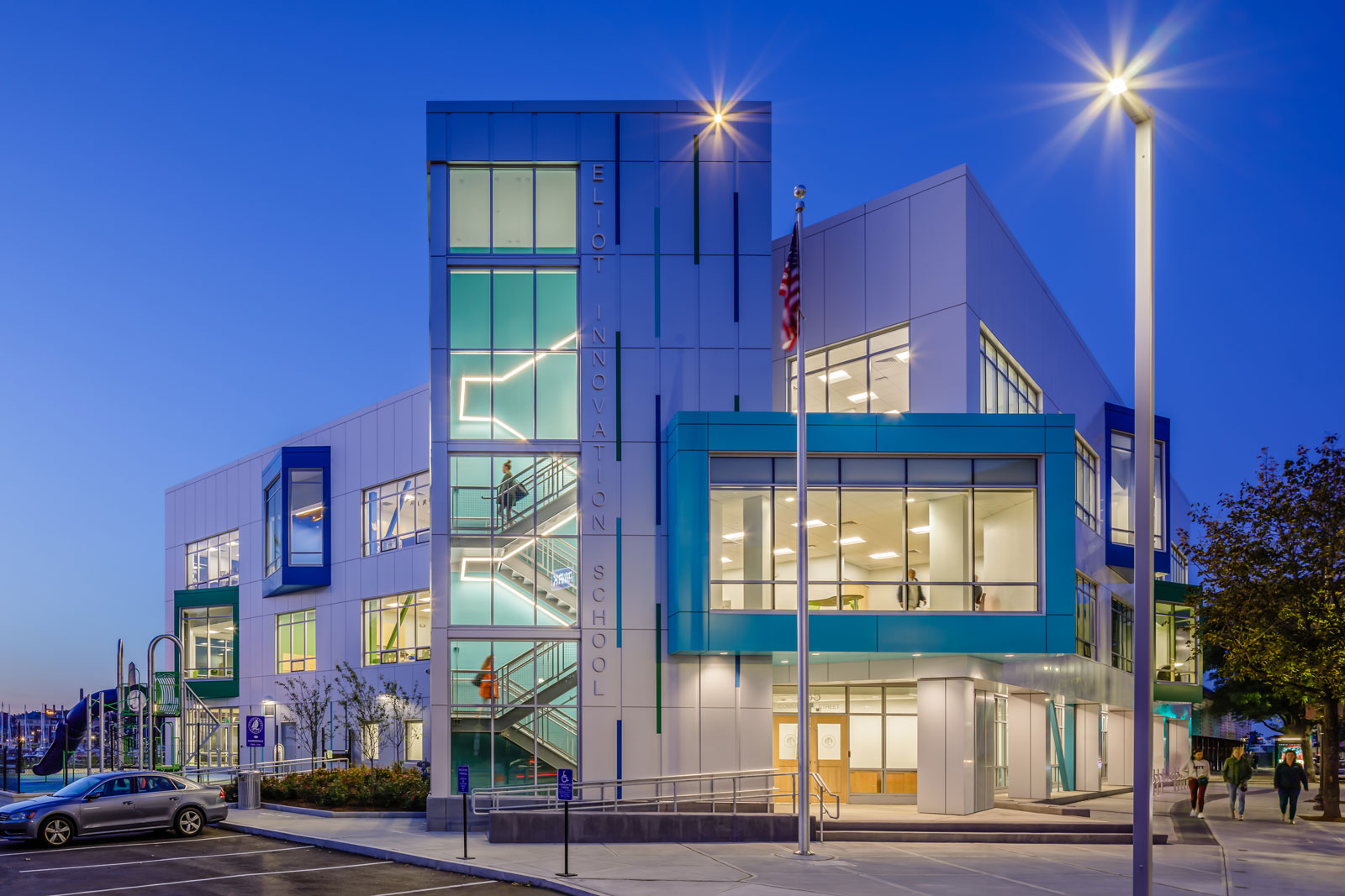 Front entrance of the Eliot Innovation School at night, lit from the interior featuring the turquoise stairway.