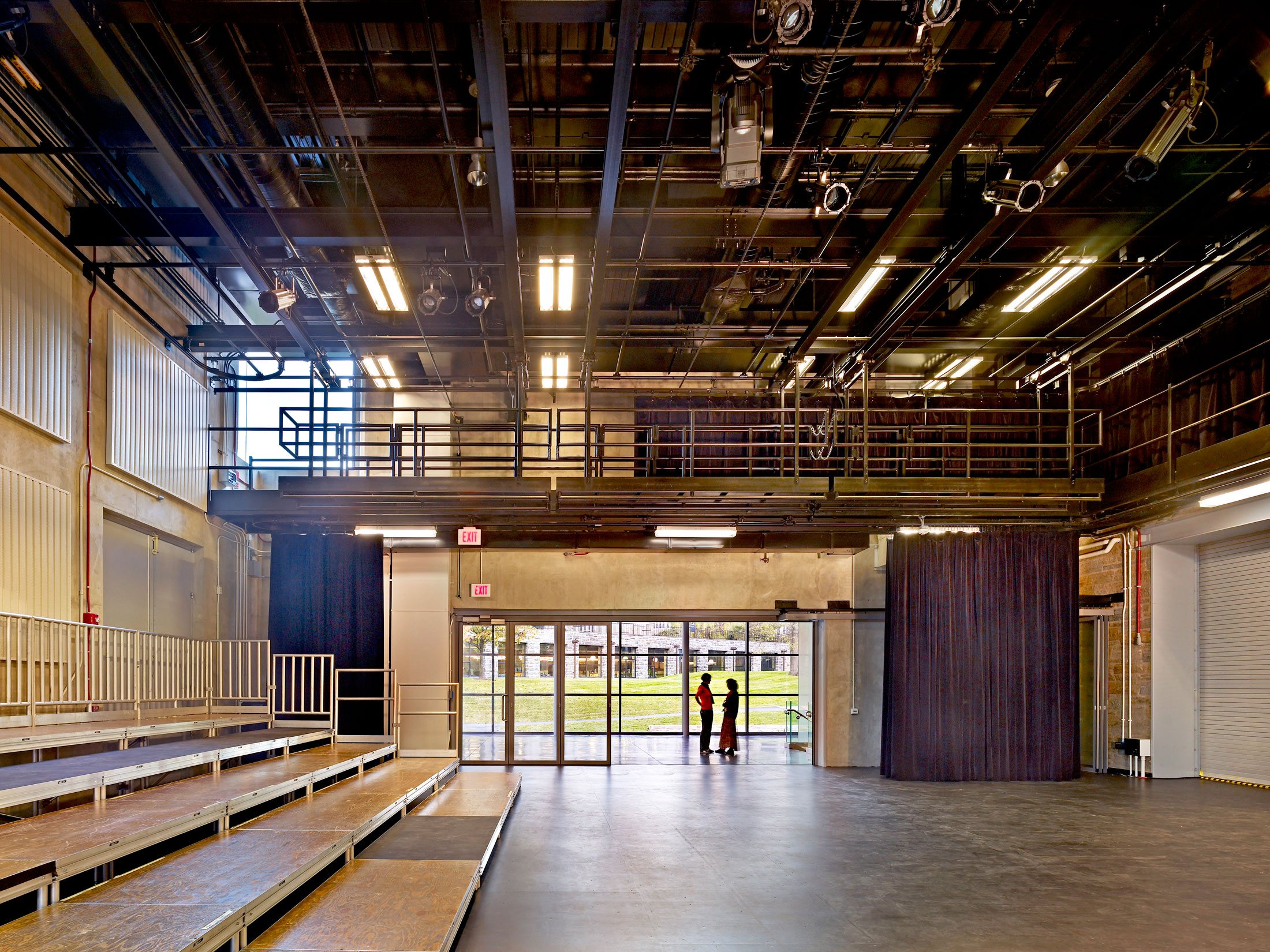 Risers to the left of interior shot of the Hepburn Teaching Theater with two students in the background near the windows.