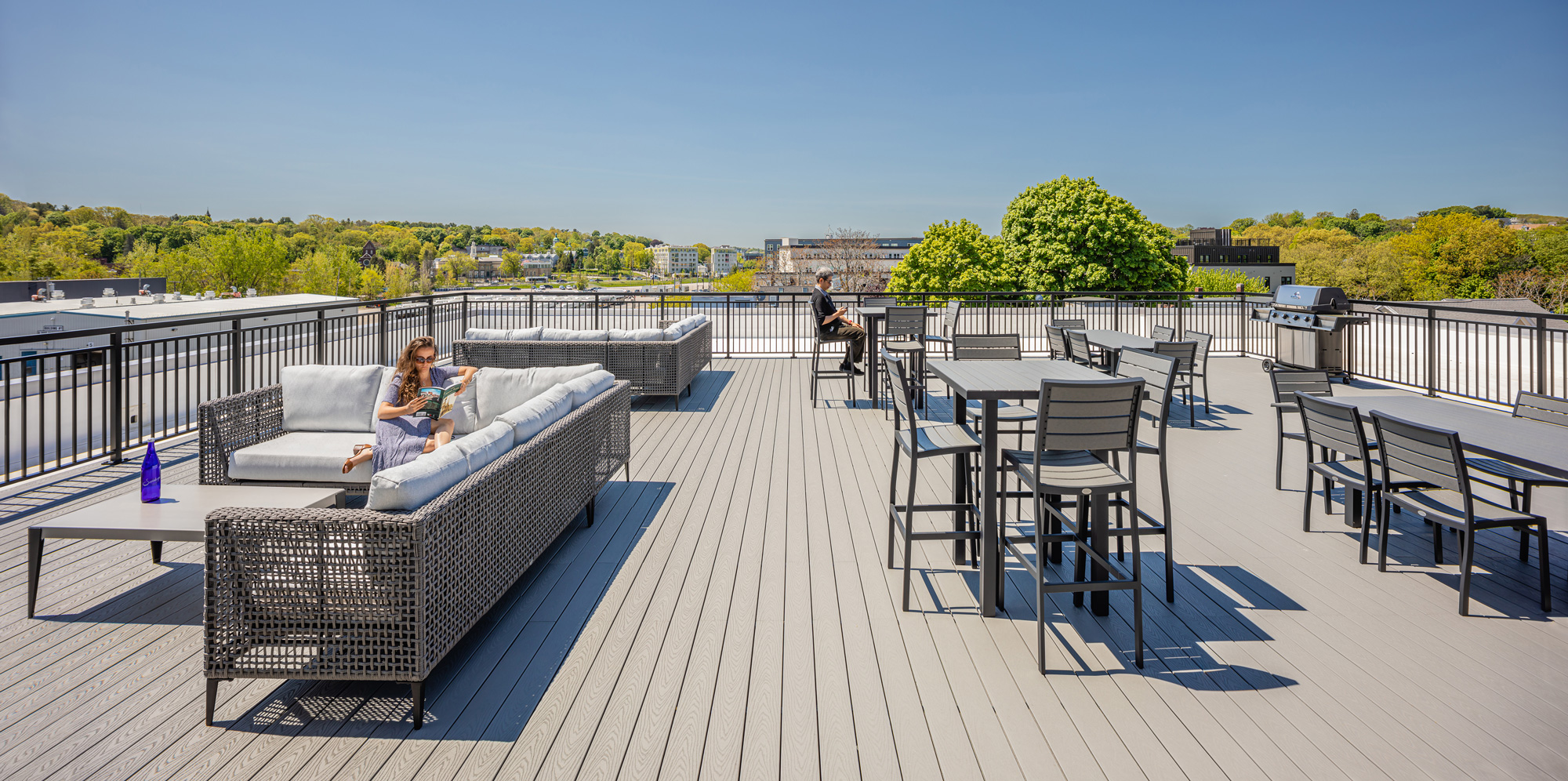 Outdoor furniture including tables, high-top tables and lounge furniture on a roof deck on a bright summer day with a woman reading on the left, and a man checking his phone in the middle.
