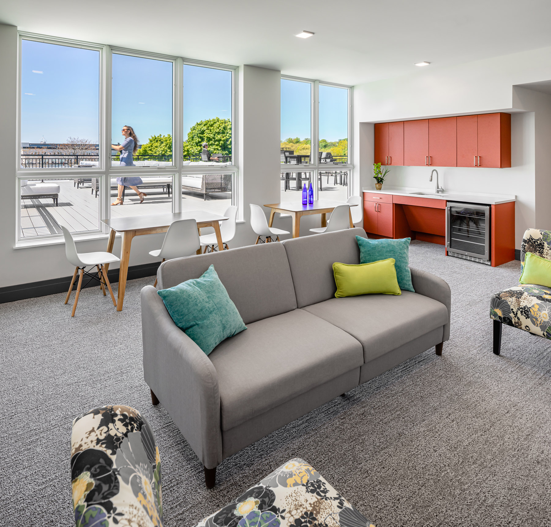 Indoor common space with lounge chairs, a couch, tables and modern chairs, and red cabinets to the right, with a view onto an outdoor roof deck.