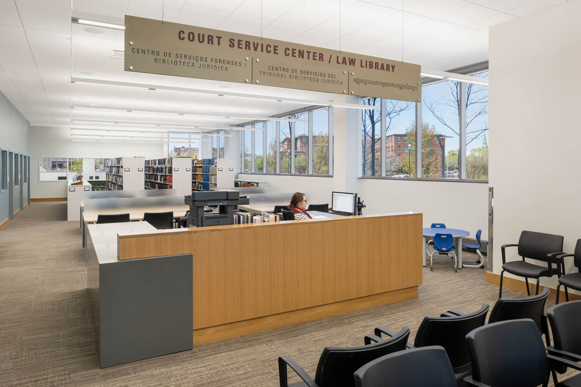 Lowell Justice Center, Court Service Center and Law Library, with a wooden service desk underneath the sign, and and brick buildings visible through the windows.