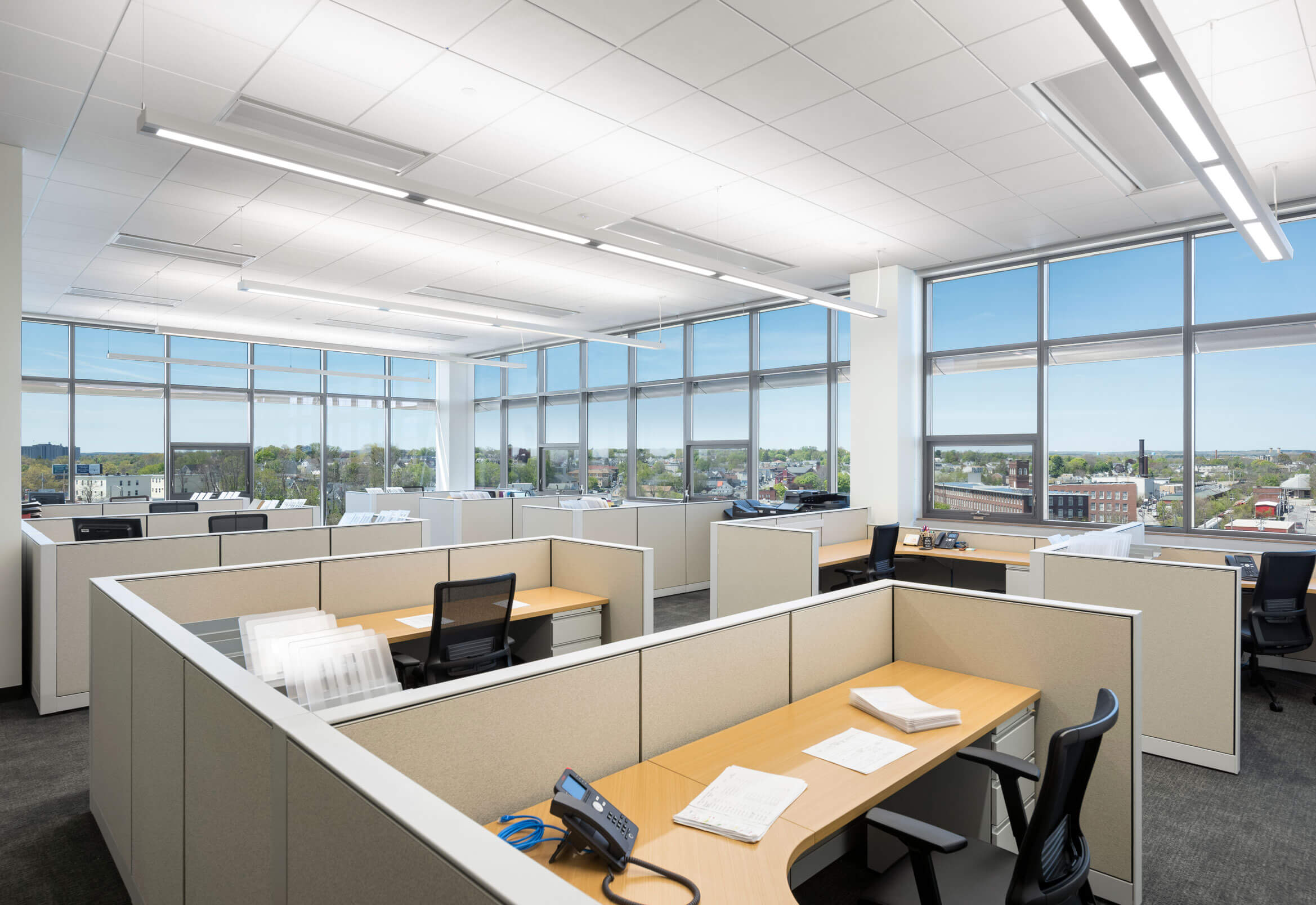 Spacious wooden office desks framed by a corner of floor-to-ceiling glass windows with a view onto the city of Lowell.
