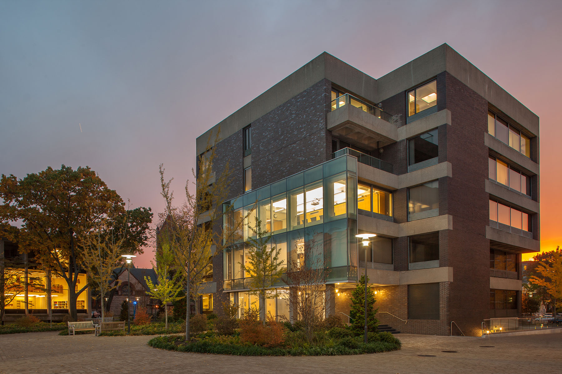 Dusk view of Pound Hall with golden light emanating from a glass facade.
