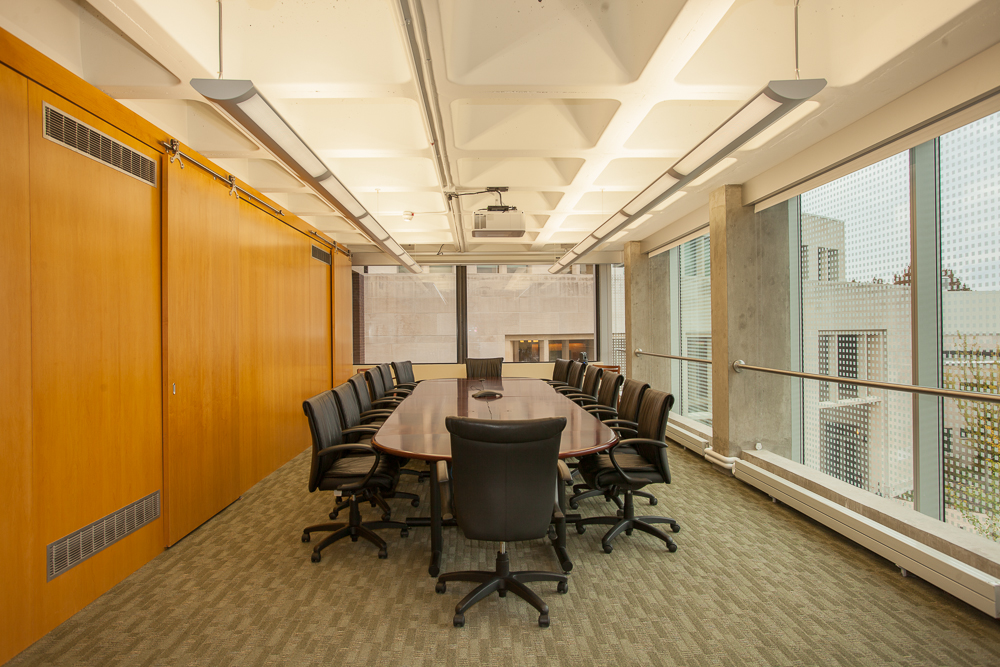 Conference room with wooden panels, a white waffle concrete slab ceiling, and windows to the right.