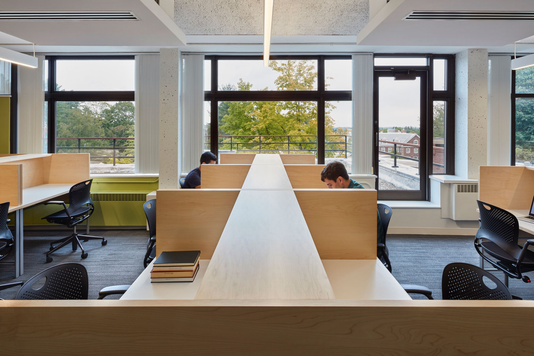 Symmetrical view over a row of study carrel, with a bright view onto green trees.