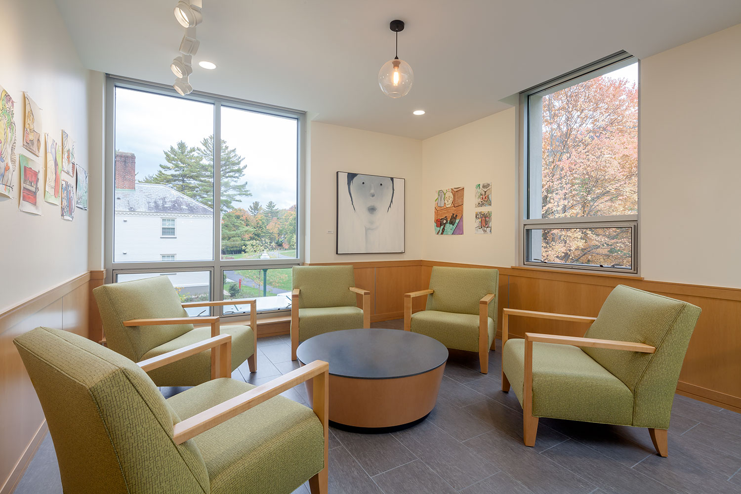 A reading nook of the building, this room has 4 green chairs with a table in the center and is framed by white walls and large windows.