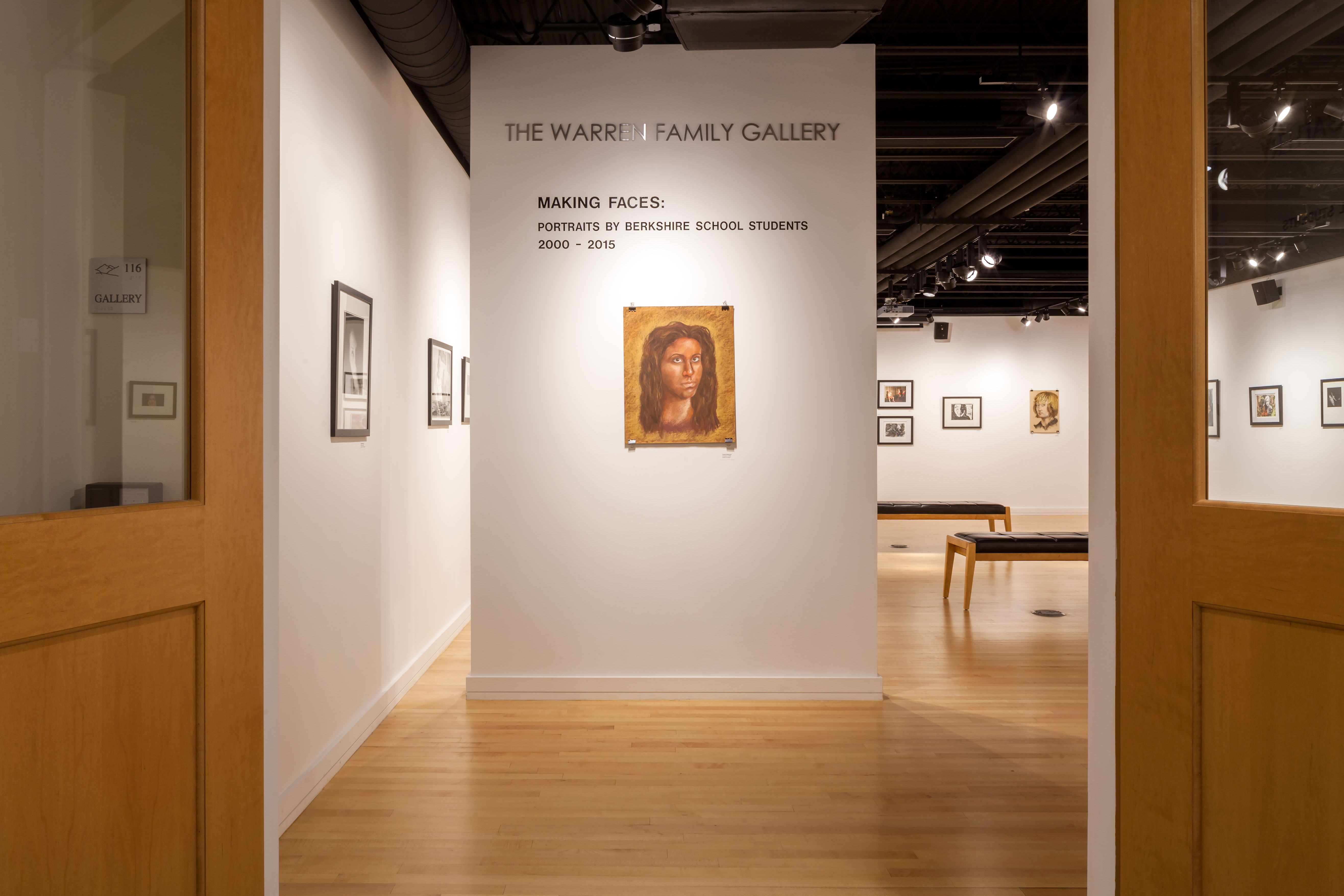 The entrance to the art gallery with open wood doors white walls, and a large freestanding wall with a student's drawing of a woman on it.