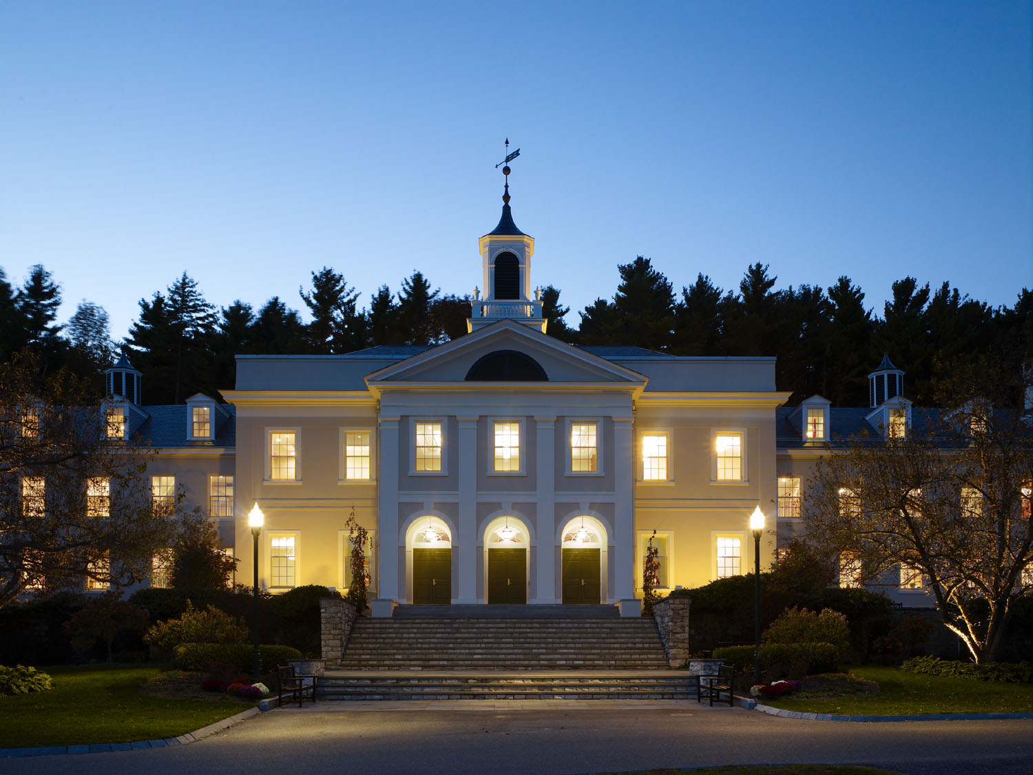 The exterior of the building: a large white building with 10 steps leading up to a front entrance with three arches and a steeple. Dark trees behind and a bright blue sky, taken at night so the building is illuminated.