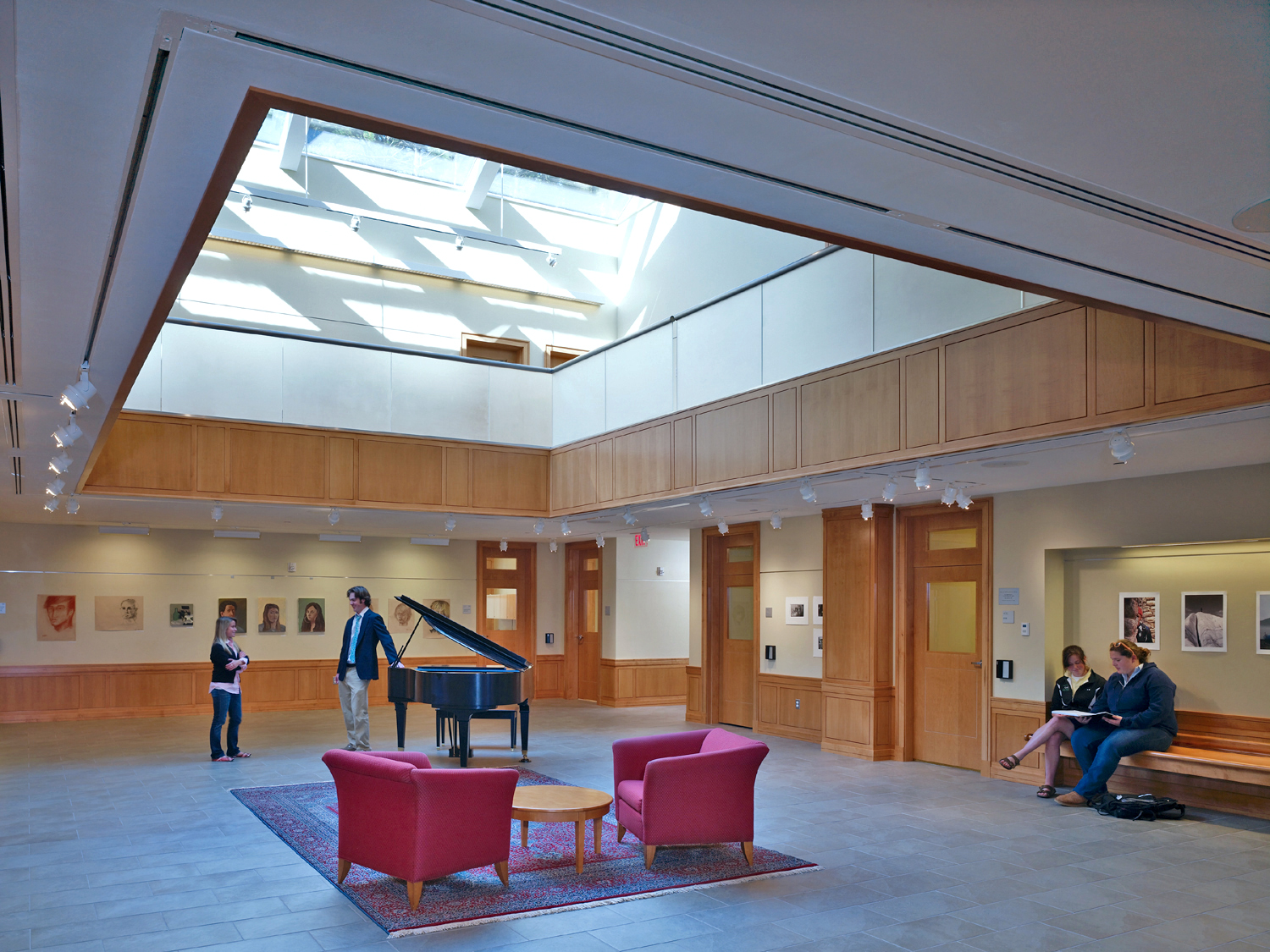 The entrance of Berkshire Hall, this image shows a wide opening in the center of a room that leads to a skylight. The room is carpeted with red chairs and a piano. Students and faculty mingle in the area.