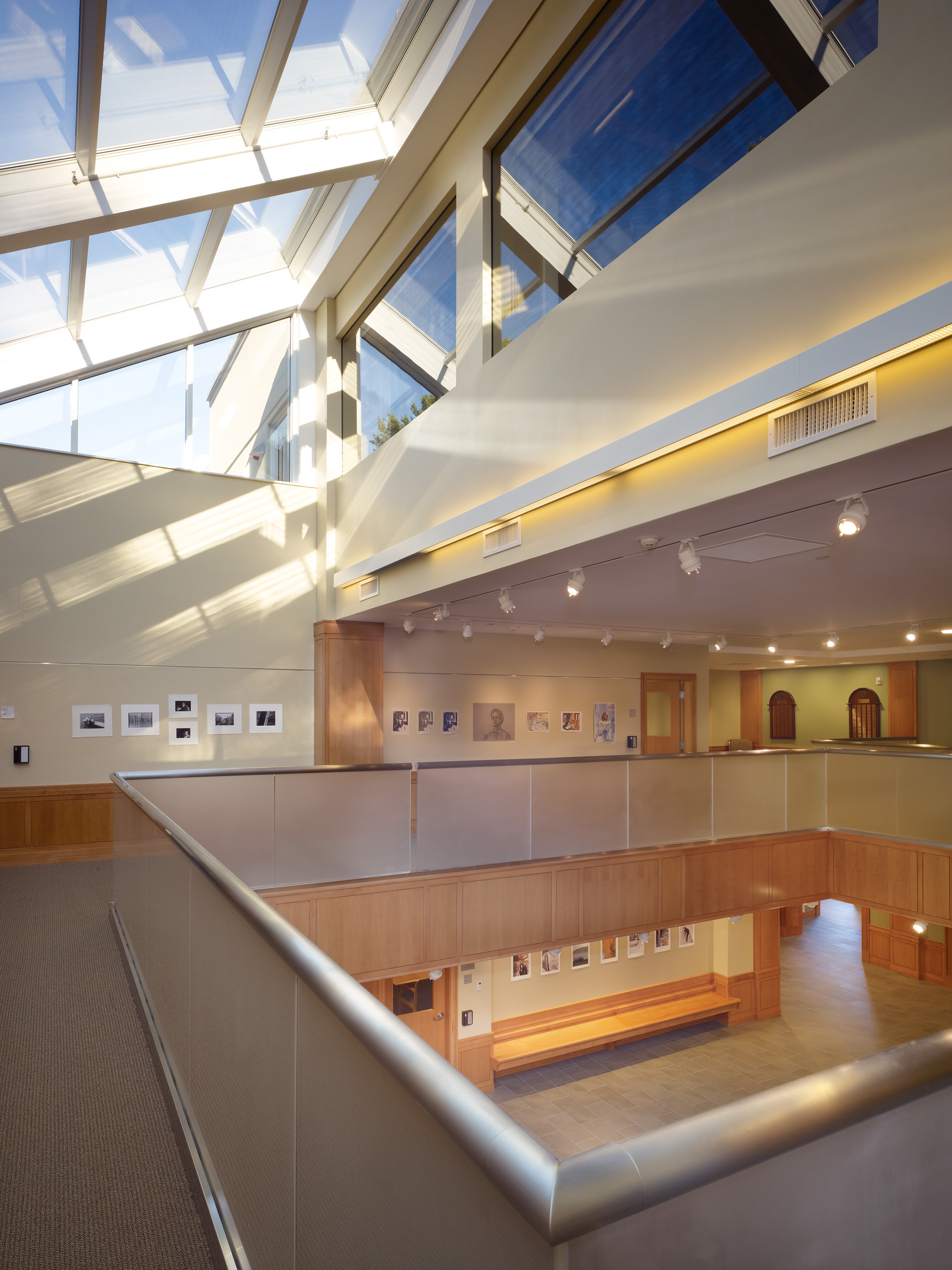 The second floor of the building, this photo shows the massive skylight that takes up almost the entire ceiling. On the floor, a large white railing runs around an opening in the floor looking into the ground level.