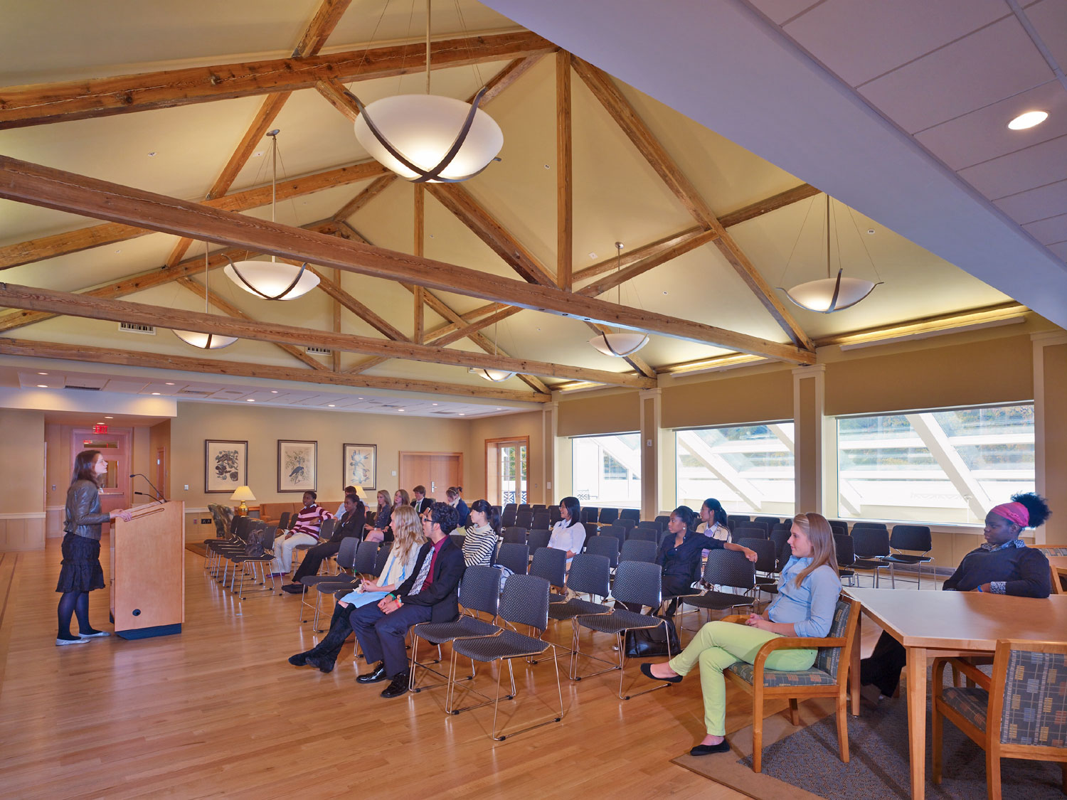 The multipurpose Great Room with large wood beams in the ceiling and a wood floor. Students and faculty sit in chairs facing a woman at a wood podium giving a speech.