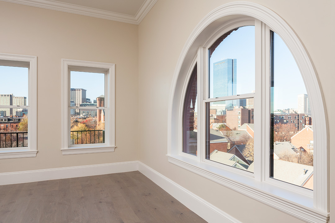 A large living room with a wood floor and beige walls. Two small rectangle windows are on the left wall and a large, half arch window shows views of Boston skyline on the right.