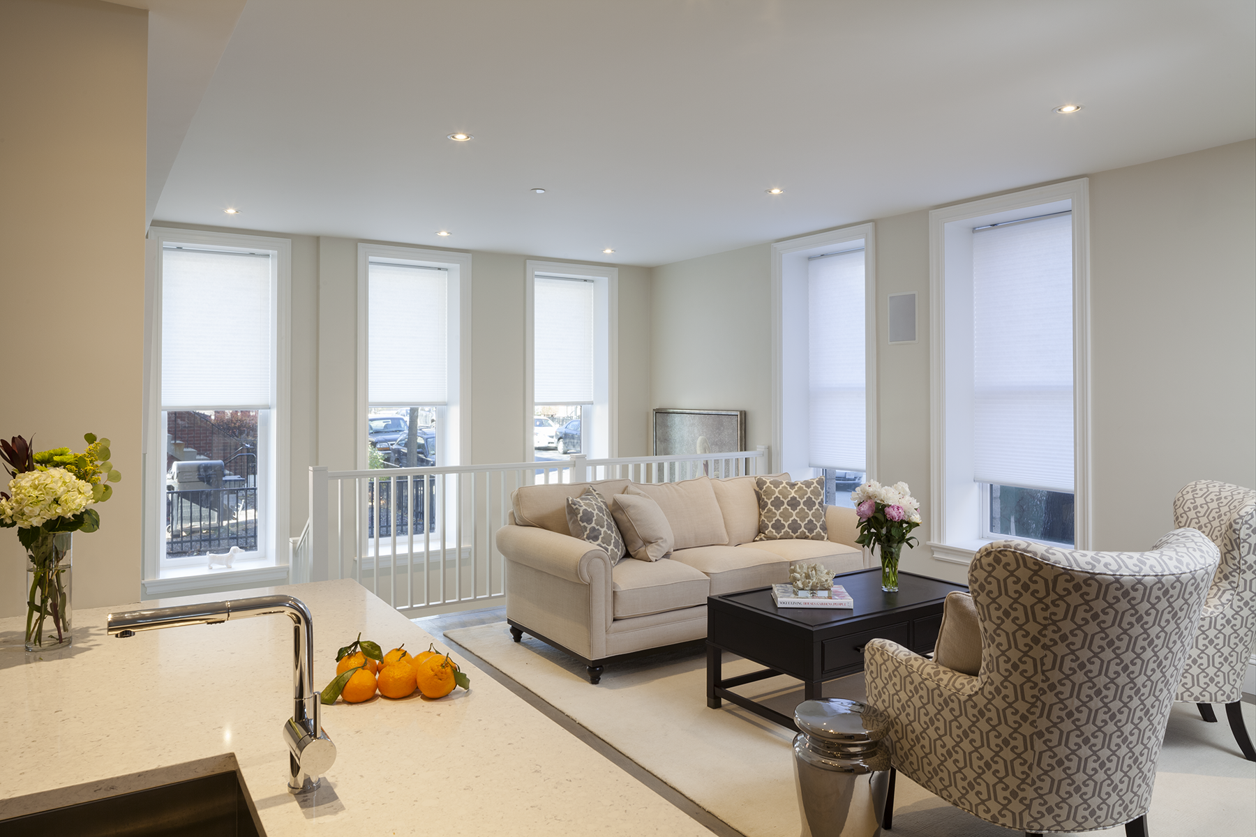 A large living room sits on the second floor with a beige couch and chair. Five large windows with white trim line the room, showing sites of the Boston skyline.