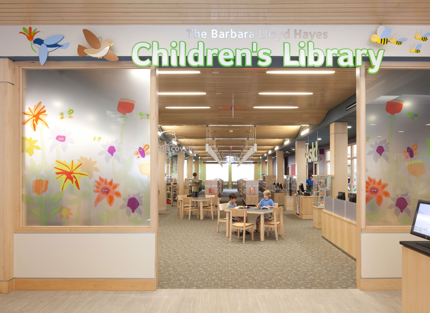 The children's library, two glass paint splattered doors frame the entrance. Inside, a grey carpet is topped with small children's tables and wood finishes.