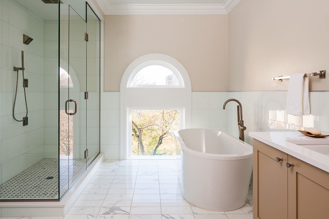A large glass shower and white tub are shown in the bathroom. Walls are light pink and a floor level arch window shows the outside Boston street.
