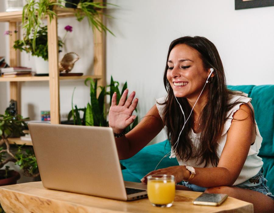Woman waving on video call.