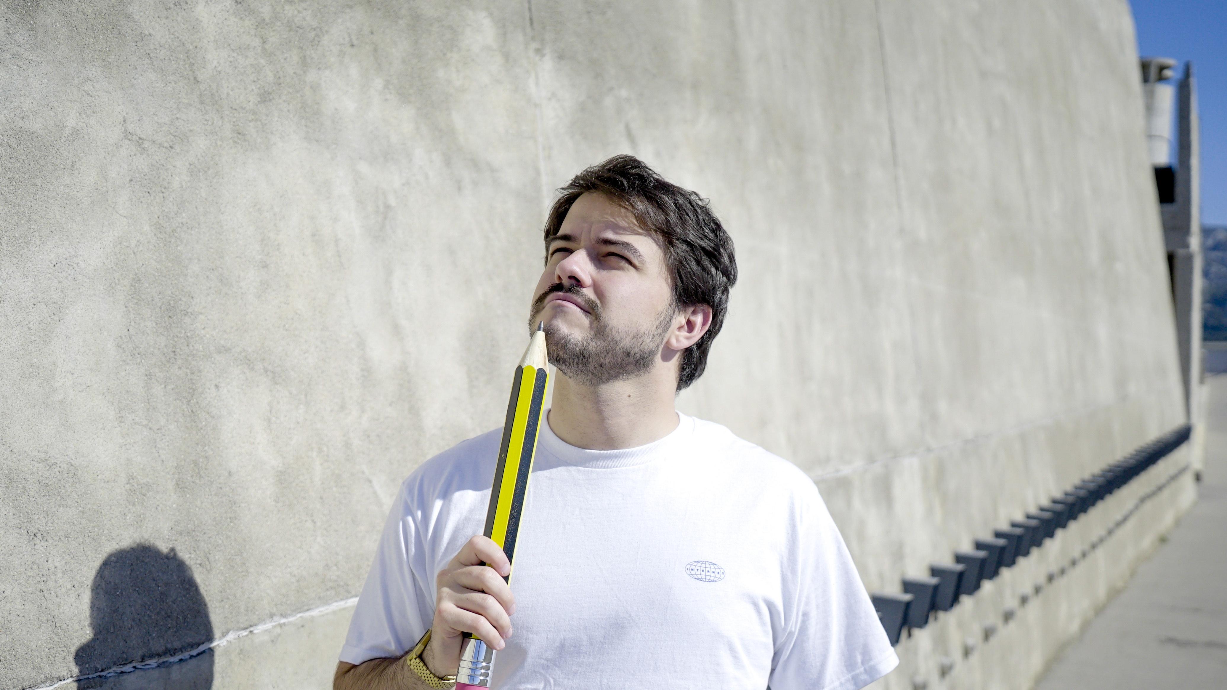 Un jeune homme tient un crayon géant.
