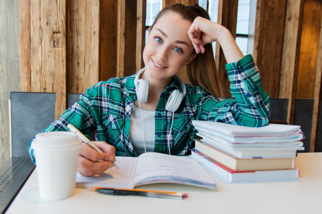 college student studying, girl with pony tail writing in book at table with arm braced on pile of books, wearing denim jacket with headphones